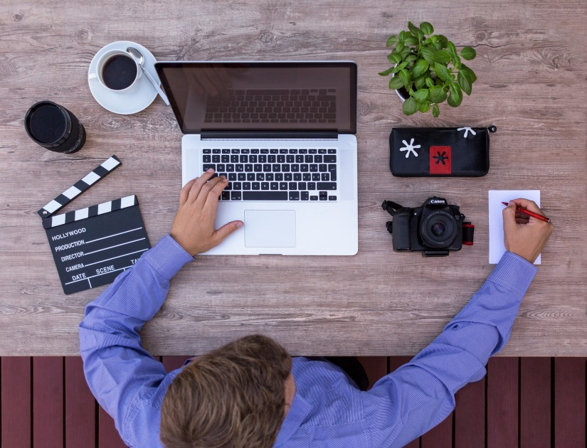 Man writing on notepad with open laptop and a clapperboard